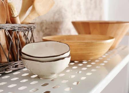 Kitchenware on shelf of storage stand
