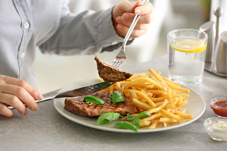Woman eating delicious grilled steak with fries in restaurant Banque d'images