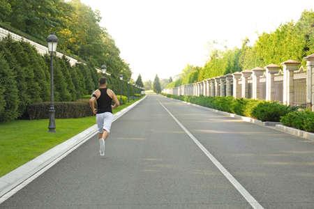 Sporty man running outdoors Stock Photo
