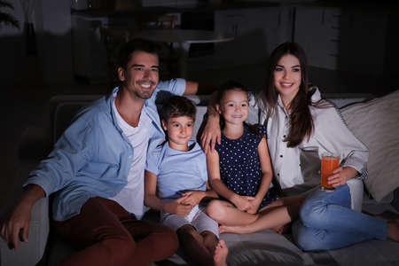 Familia feliz viendo la televisión en el sofá por la noche
