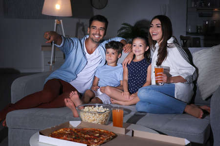 Tv kijken op de bank 's nachts en gelukkige familie Stockfoto - 101882485