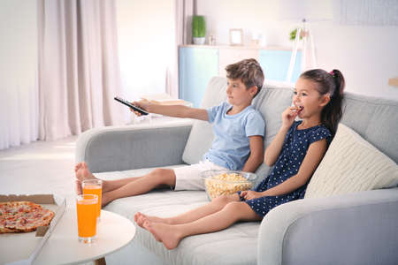 Cute children watching TV on sofa at home