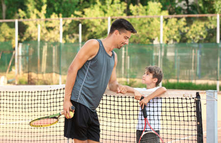 Young trainer with little boy on tennis court