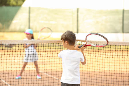 Cute little children playing tennis on court