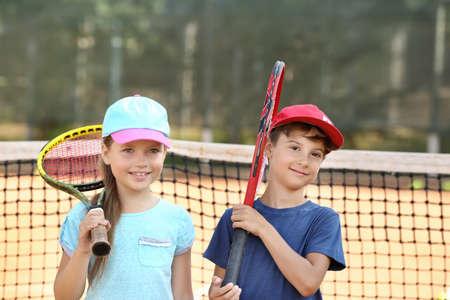 Cute little children on tennis court