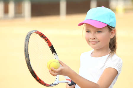 Cute little girl playing tennis on court
