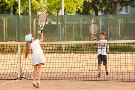 Cute little children playing tennis on court