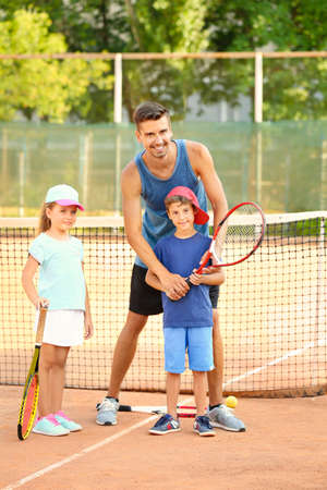 Young trainer with little children on tennis court Stok Fotoğraf