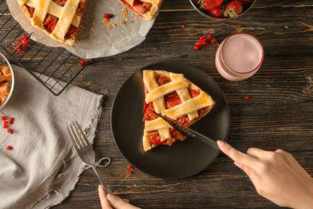 Woman cutting piece of tasty strawberry rhubarb pie on table