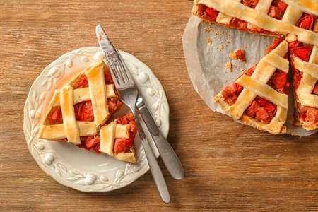 Plate with piece of tasty strawberry rhubarb pie on table