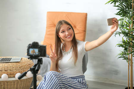 Young female blogger recording video in room