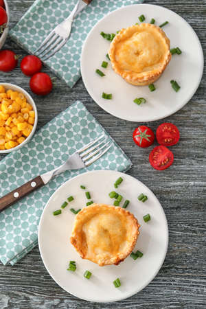 Plates with delicious meat mini pies on table