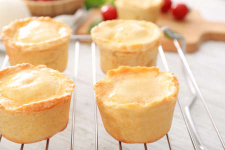 Delicious meat mini pies on baking grid, closeup