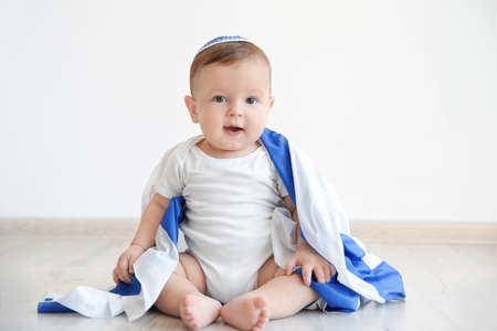 Cute baby with flag of Israel sitting on floor at home