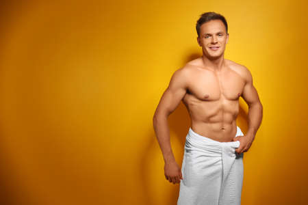 Muscular man wrapped in towel, on color background
