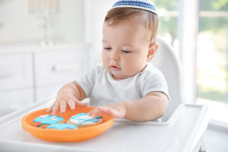 Cute baby eating festive cookies while sitting on high chair Stock Photo