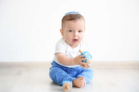 Cute baby in kippah playing with dreidels while sitting on floor at home Stock Photo
