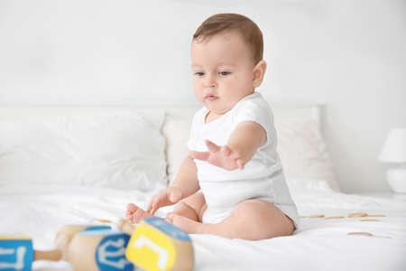 Cute baby playing with dreidels on bed
