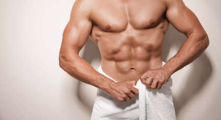 Muscular man wrapped in towel, on light background Stock Photo