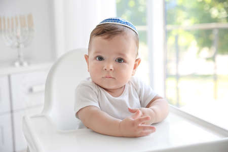 Cute baby in kippah sitting on high chair at home