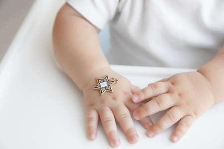 Star of David pendant on hand of baby, closeup