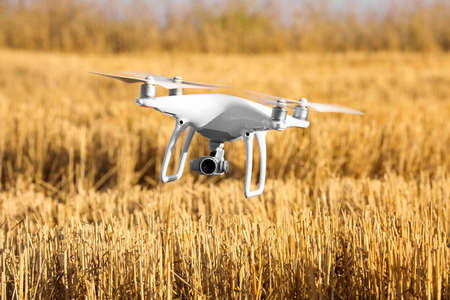 Modern quadcopter flying over field Stock Photo