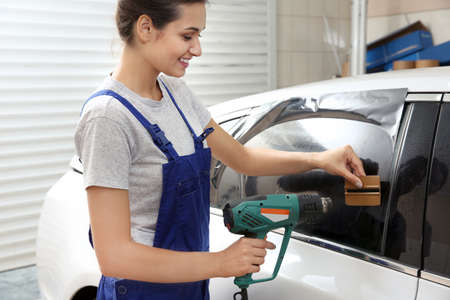Female worker tinting car window Stock Photo