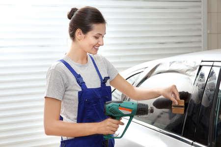 Female worker tinting car window Stock Photo
