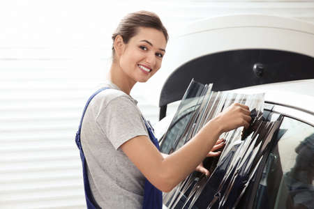 Female worker applying tinting foil onto car window in shop