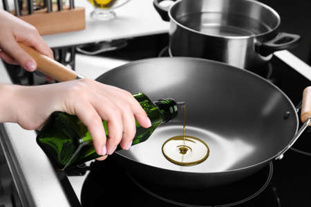 Stock Photo   Woman Pouring Oil From Bottle Onto Wok In Kitchen
