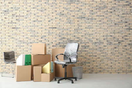 Office move concept. Carton boxes and chairs near brick wall in empty room
