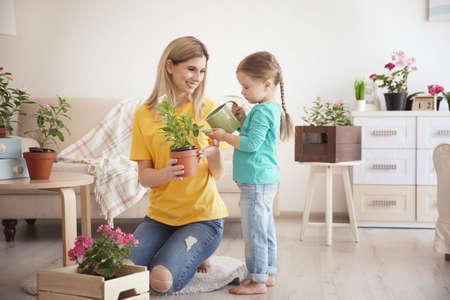 Bambina sveglia con la madre che prende cura delle piante all'interno Archivio Fotografico - 98773712