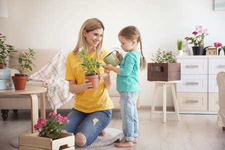 Cute little girl with mother taking care of plants indoors