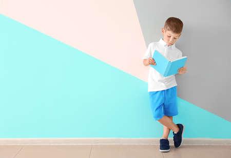 Cute little boy reading book near color wall