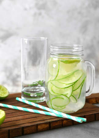 Jar with detox infused cucumber water on wooden board