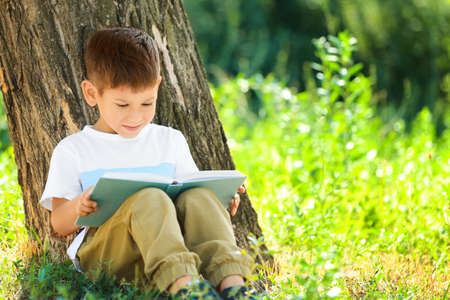 Cute little boy reading book in park