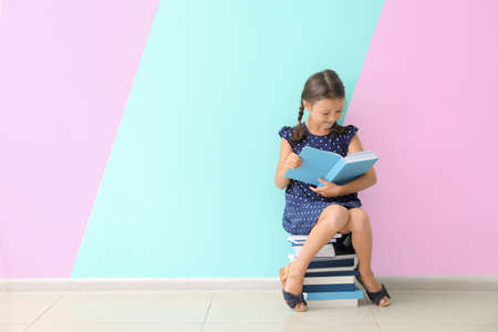 Cute little girl reading books near color wall