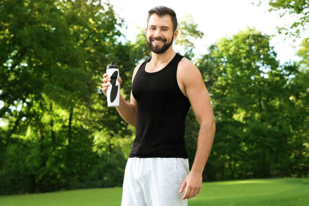 Sporty young man with bottle of water outdoors Stock Photo