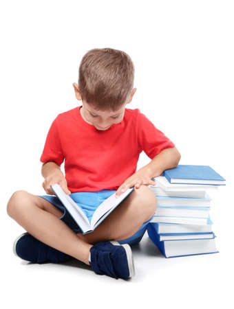 Cute little boy reading books on white background