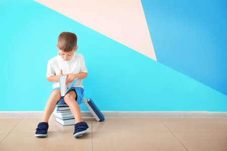 Cute little boy reading books near color wall