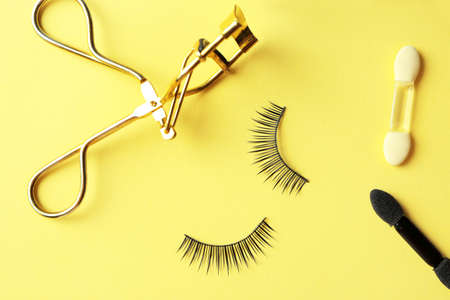 Composition with curler and false eyelashes on color background