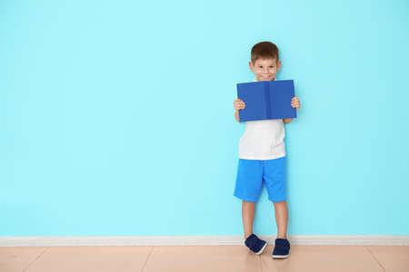 Cute little boy with book near color wall