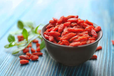 Bowl with red dried goji berries on wooden table Imagens