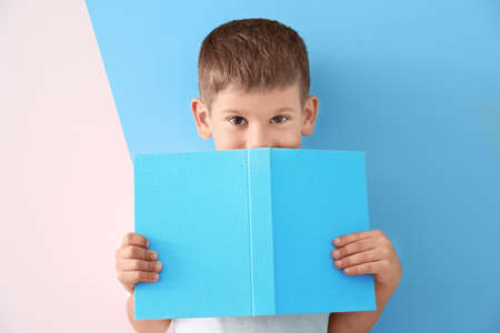 Cute little boy with book on color background