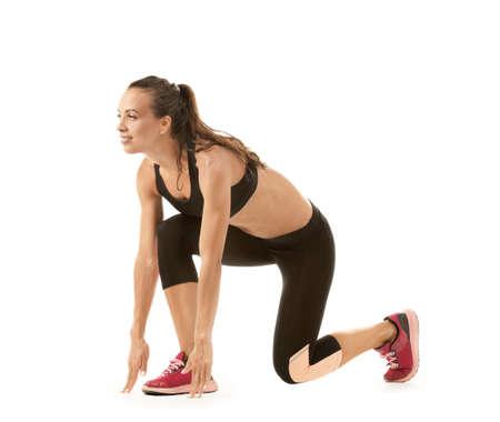Beautiful young woman in sportswear preparing to run, on white background