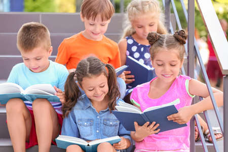 Cute little children reading books while sitting on steps outdoors