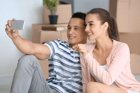 Happy young couple taking selfie in their new apartment