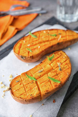 Cutting board with baked sweet potato on table