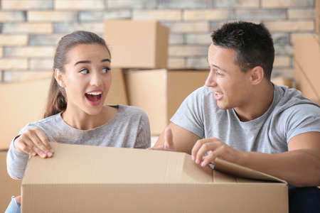 Happy young couple with moving box in their new apartment Stock Photo