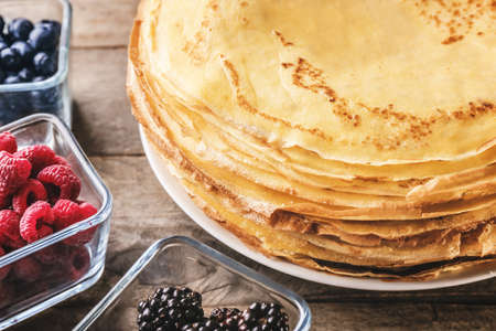 Stack of delicious thin pancakes on plate served with berries, closeup